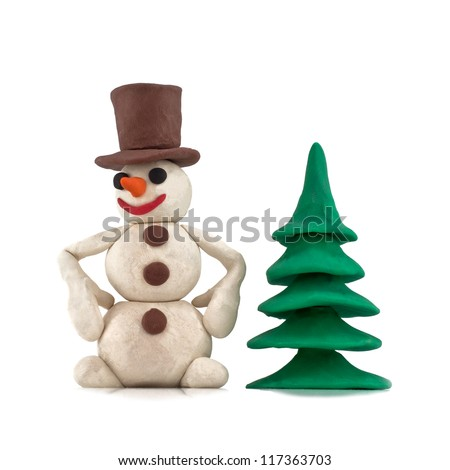 plasticine snowman standing near the Christmas tree isolated on white background - stock photo