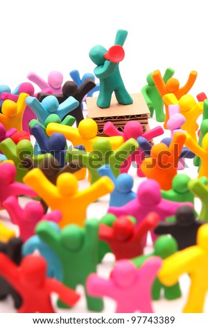 plasticine speaker standing on podium talking to his crowd through red megaphone - isolated on white - stock photo