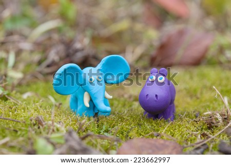 Plasticine world - little homemade blue elephant and purple hippo on a green background , selective focus and place for text - stock photo