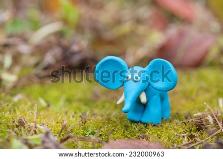 Plasticine world - little homemade blue elephant on a green background , selective focus and place for text - stock photo