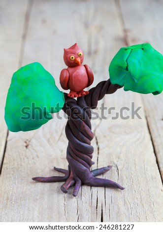 Plasticine world - little homemade brown owl with yellow eyes sitting on a tree on a wooden background, selective focus and place for text  - stock photo