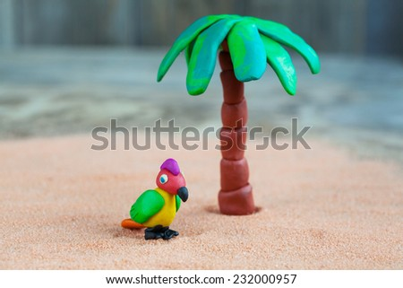 Plasticine world - little homemade multicolored parrot and palm on a wooden background, selective focus and place for text - stock photo