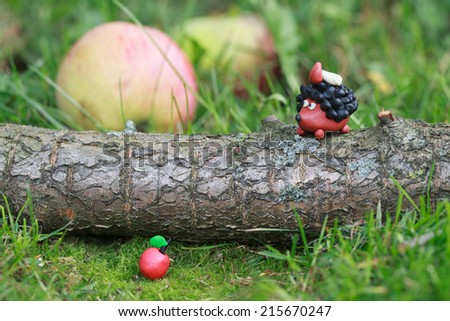 Plasticine world - small homemade hedgehog sitting on tree trunk with boletus on his back on a green meadow surrounded plasticine apples, selective focus on the hedgehog - stock photo