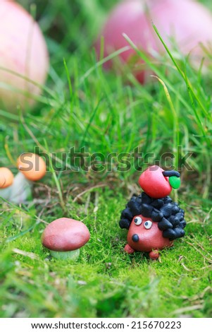 Plasticine world - small homemade hedgehog with apple on his back on a green meadow surrounded plasticine mushrooms, selective focus on the hedgehog - stock photo