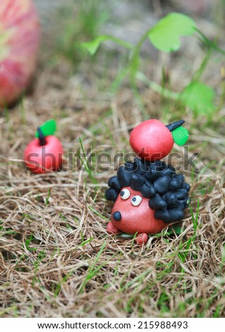 Plasticine world - small homemade hedgehog with apple on his back on a green meadow surrounded plasticine red apples, selective focus on the hedgehog - stock photo