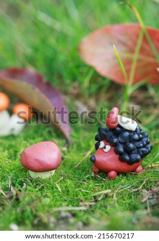 Plasticine world - small homemade hedgehog with boletus on his back on a green meadow surrounded plasticine mushrooms, selective focus on the hedgehog - stock photo