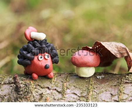 Plasticine world - small homemade hedgehog with boletus on his back sitting sitting next to a mushroom under a fallen autumn leaf, selective focus on head - stock photo