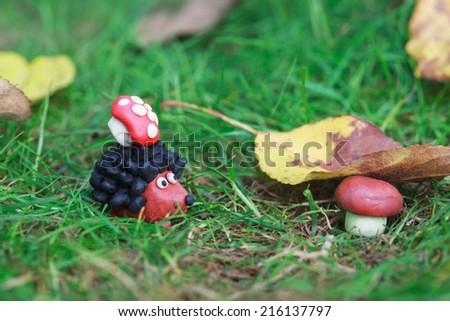 Plasticine world - small homemade hedgehog with fly agaric found boletus mushroom under a fallen autumn leaf, selective focus on the hedgehog  - stock photo