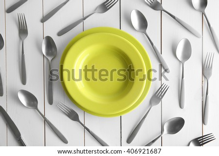 Plate and silver flatware on white table, top view - stock photo