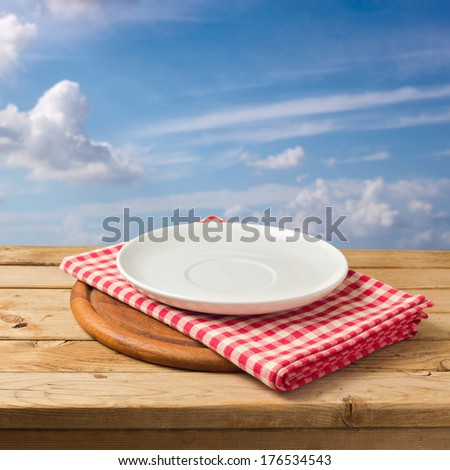 Plate and tablecloth on wooden table over blue sky - stock photo