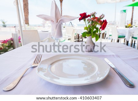 Plate, fork, knife, napkin and flowers on the cafe  table.  - stock photo