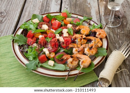 Plate of a grilled shrimp salad with feta cheese, tomatoes, and watermelon in a rustic setting.  - stock photo