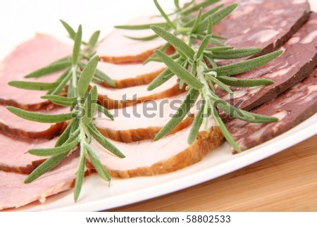 Plate of assorted cold cuts (ham, sirloin, headcheese) decorated with rosemary - stock photo