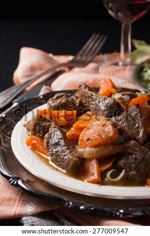 Plate of beef stew with a green salad on dark background. Very Shallow depth of field. - stock photo