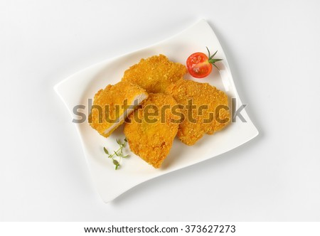 plate of breaded turkey breasts on white background - stock photo