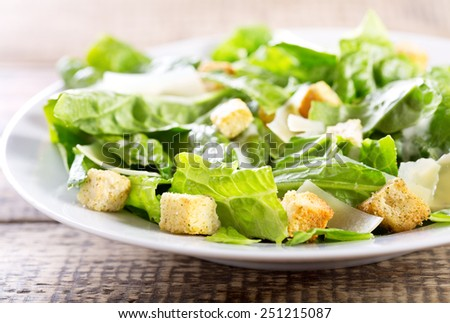 plate of caesar salad on wooden table - stock photo