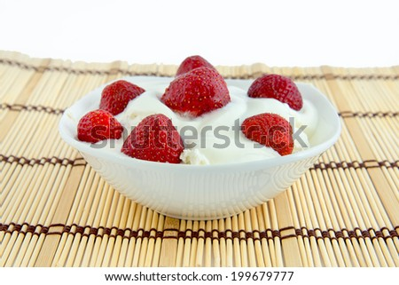 Plate of cheese with sour cream and strawberries is on the table. - stock photo