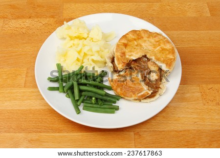 Plate of Chicken pie mashed potato and green beans on a wooden tabletop - stock photo