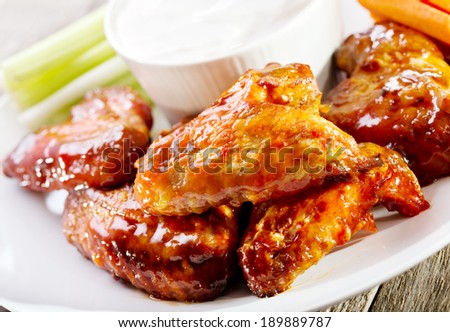 plate of chicken wings on wooden table - stock photo