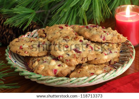 Plate of cranberry cookies lit by candle light - stock photo