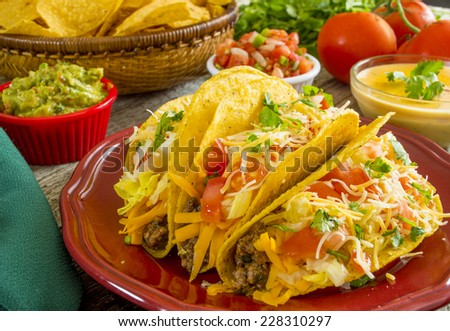 "plate of crispy beef tacos with guacamole and cheese dip ""crispy beef taco dinner"" - stock photo"