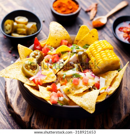 Plate of delicious tortilla nachos with melted cheese sauce, chicken, jalapeno peppers, red onion, green onions, tomato, salsa and corn cobs. - stock photo