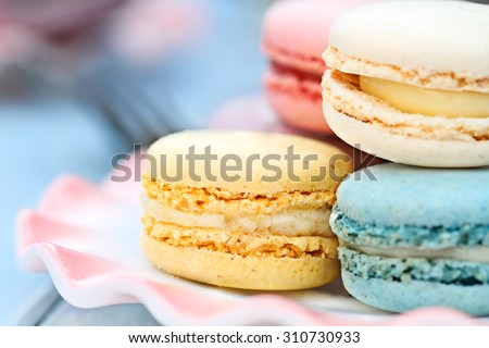 Plate of fresh colorful macarons. Extreme shallow depth of field with selective focus on yellow lemon macaron. - stock photo