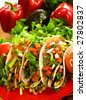Plate of freshly prepared ground beef tacos, with tomato, freshly grated cheese, lettuce and sour cream. - stock photo