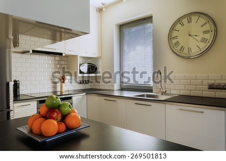 Plate of fruits on the kitchen worktop - stock photo
