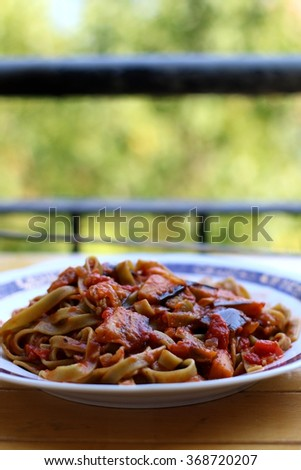 Plate of green pasta with sliced zucchini and tomato sauce. Selective focus, copy space.  - stock photo