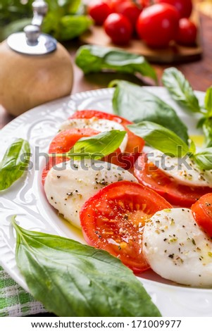 Plate of Healthy Classic Caprese Salad with Mozzarella Cheese, Tomatoes and Basil - stock photo