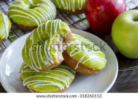 Plate of homemade baked caramel apple donuts with green apple glaze with bite out of top donut sitting on white plate with fresh apples in background - stock photo