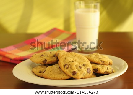 Plate of homemade chocolate chip cookies served with milk. - stock photo