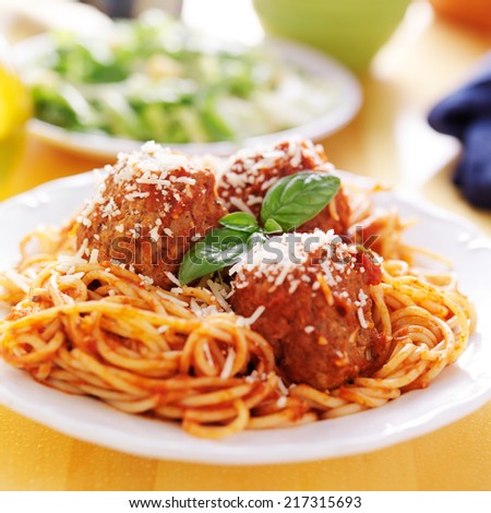 plate of italian spaghetti and meatballs covered in sauce - stock photo