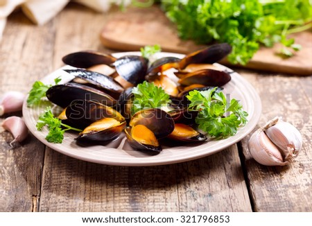 plate of mussels with parsley on wooden table - stock photo