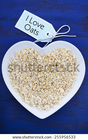 Plate of nutritious and healthy oat flakes in heart shaped bowl on dark blue rustic wood table, with I Love Oats message tag, vertical. - stock photo