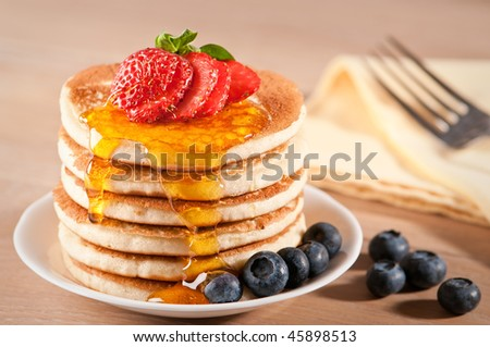 Plate of pancakes dripping with maple syrup with strawberry and blueberries - stock photo