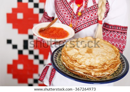plate of pancakes in the hands of a girl in national costume - stock photo