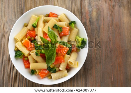 Plate of pasta with salmon and broccoli on wooden table, top view - stock photo