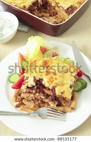 Plate of pastitsio meat and pasta topped with bechamel sauce and cheese, tomato, cucumber and lettuce salad and the serving bowl. - stock photo