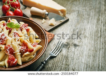 Plate of penne pasta with tomato sauce and parmesan cheese - stock photo