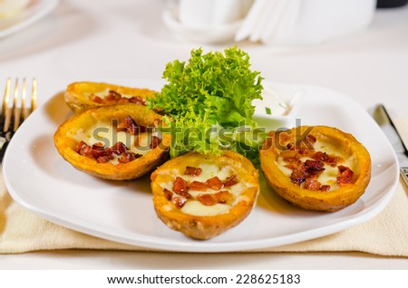 Plate of Potato Skins with Cheese and Bacon Appetizer Served in Restaurant - stock photo