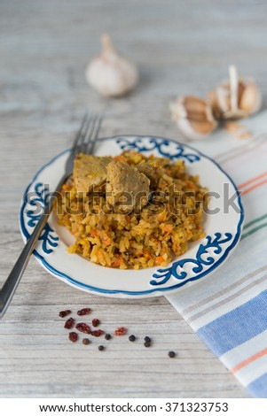 Plate of rice and meat national dish pilau with spices - stock photo