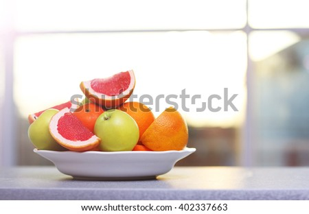 Plate of ripe fruits on a table - stock photo