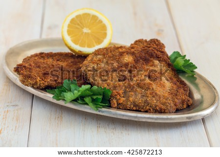 Plate of schnitzel with lemon and parsley on a wooden table. - stock photo