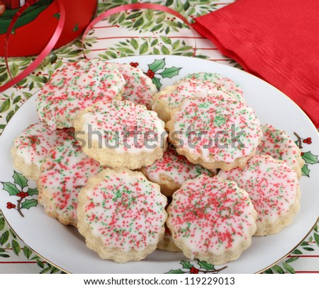 Plate of shortbread Christmas cookies with icing and colored sprinkles - stock photo