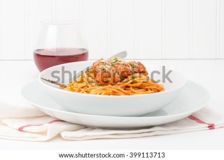 Plate of spaghetti and meatballs topped with fresh herbs and parmesan cheese. - stock photo