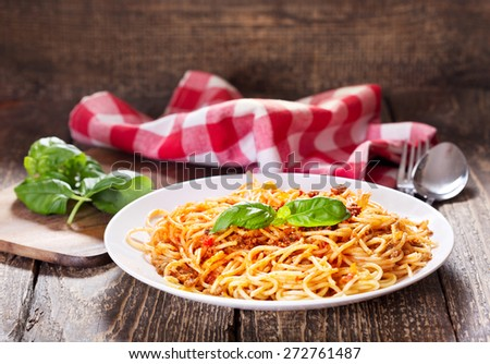 plate of spaghetti bolognese on wooden table - stock photo
