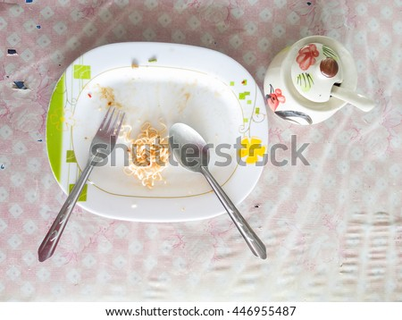 Plate of spaghetti noodle at the end of a meal on a table - stock photo