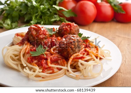 plate of spaghetti with meatballs in tomato marinara sauce and ingredients on a wooden table - stock photo